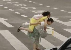 Carga a niña en muletas para ayudarla a cruzar la calle