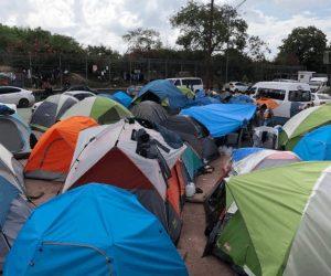 Migrantes saturan puente; luce abarrotado de tiendas de campaña